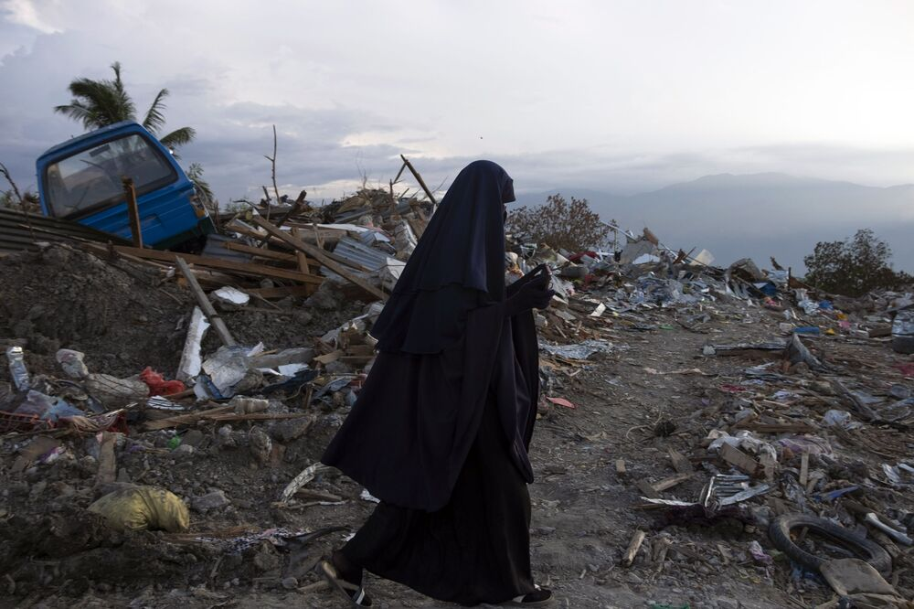Mulher indonésia passa por zona destruída na aldeia de Petobo, em Palu, após o terremoto e tsunami que abalaram o local