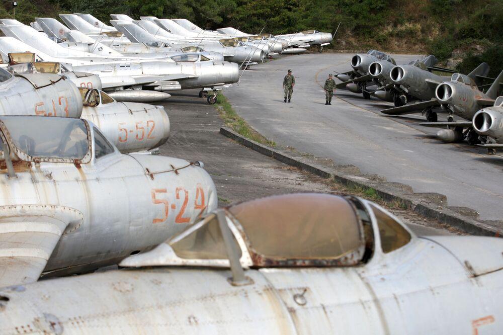 Militares da Força Aérea albanesa caminhando ao lado de caças MiG na base aérea de Kucove