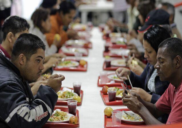 Pessoas comem em restaurante popular patrocinado pelo governo do Brasil no âmbito do Programa Fome Zero, São Paulo, 22 de julho de 2011