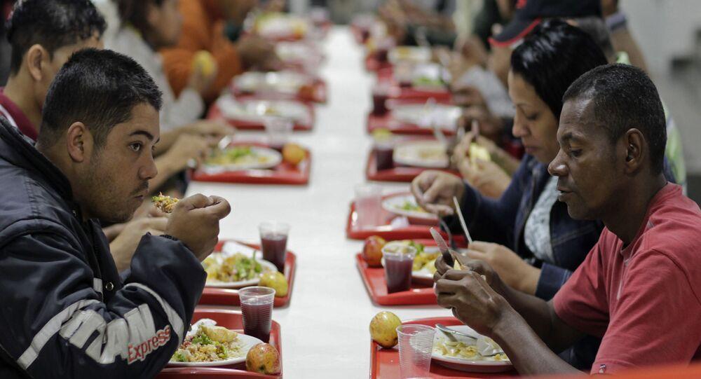 Pessoas comem em restaurante popular patrocinado pelo governo federal brasileiro no âmbito do Programa Fome Zero, São Paulo, 22 de julho de 2011