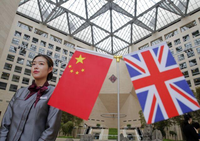 Um membro da equipe de pé atrás de bandeiras enquanto os oficiais chegam para a Mesa Redonda de Serviços Financeiros de Alto Nível Reino Unido-China no prédio da sede do Banco da China em Pequim (arquivo).