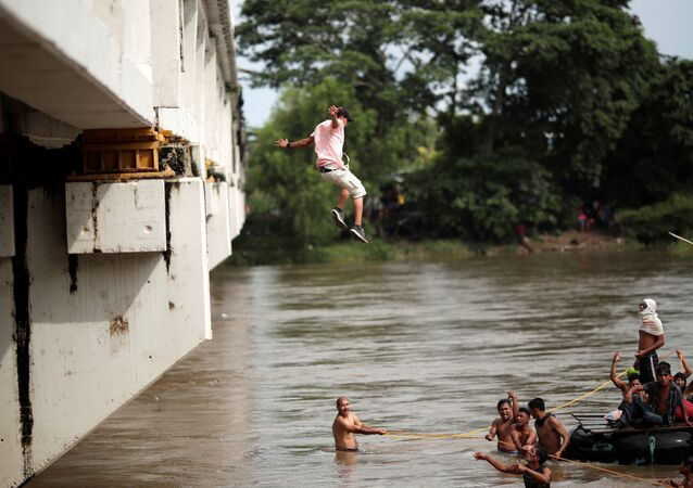 Um migrante hondurenho salta da ponte que liga México e Guatemala para evitar o posto fronteiriço em Ciudad Hidalgo