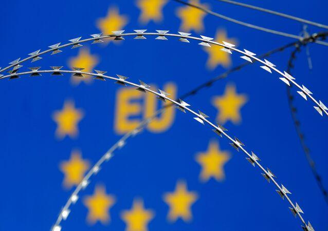 Arame farpado visto na frente da logo da União Europeia (UE) durante um protesto contra cercas ao longo da passagem fronteiriça entre Eslovênia e Croácia.