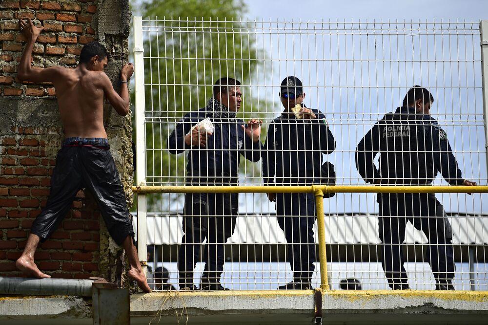 Imigrante das Honduras rumo aos EUA, prestes a saltar para o rio Suchiate da ponte fronteiriça internacional entre a Guatemala e o México.