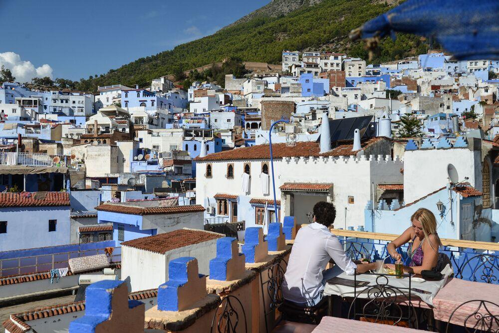 Pessoas tomando refeição no terraço de uma cidade de Marrocos