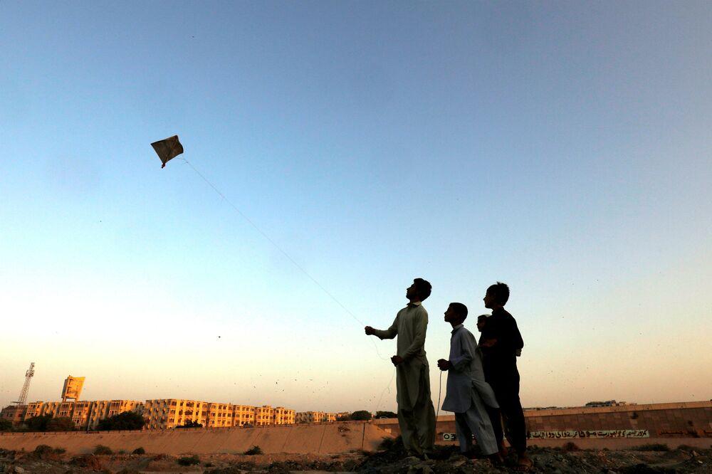 Crianças paquistanesas lançando uma pipa