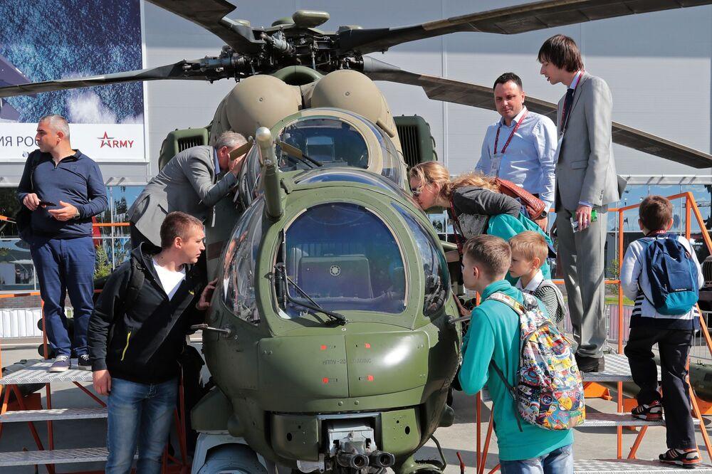 Visitantes do fórum técnico-militar internacional EXÉRCITO 2018 perto de um helicóptero Mi-35M