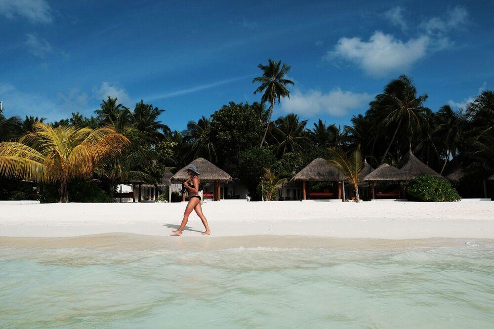 Moça caminhando em praia das ilhas Maldivas