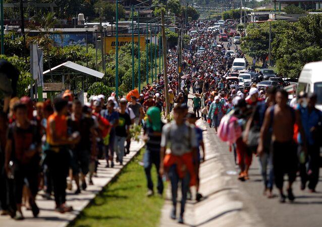 Migrantes da América Central caminham ao longo da estrada perto da fronteira com a Guatemala, enquanto continuam sua jornada tentando alcançar os EUA.