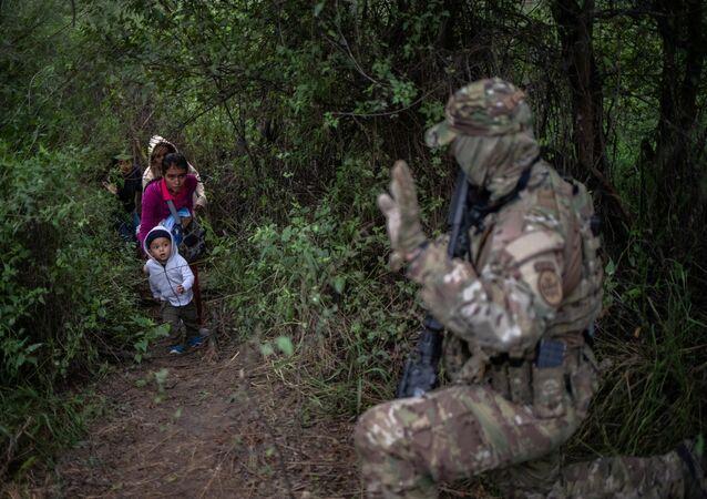 Um membro da Unidade Tática de Patrulha de Fronteira dos EUA (BORTAC) interpela uma família que cruza ilegalmente a fronteira entre o México e os EUA.