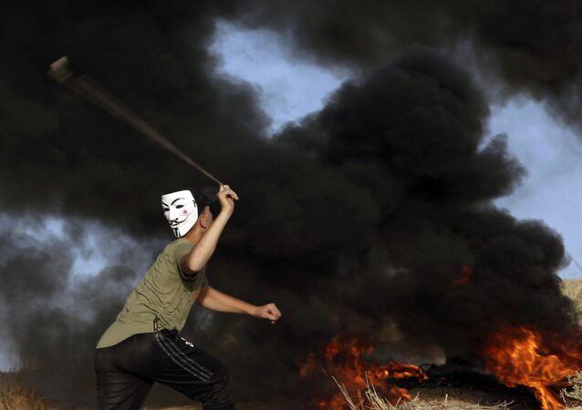 Manifestante usando máscara arremessa pedras contra as tropas israelenses perto da fronteira da Faixa de Gaza com Israel durante protesto, em 29 de outubro de 2018
