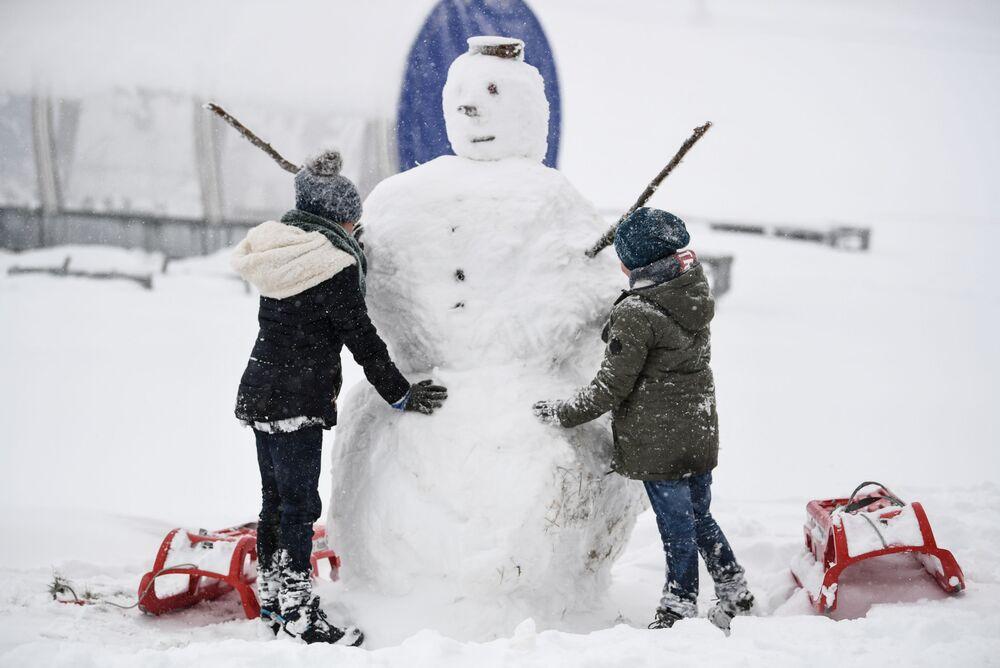 Crianças constroem boneco de neve na Alemanha após nevasca, em 28 de outubro de 2018
