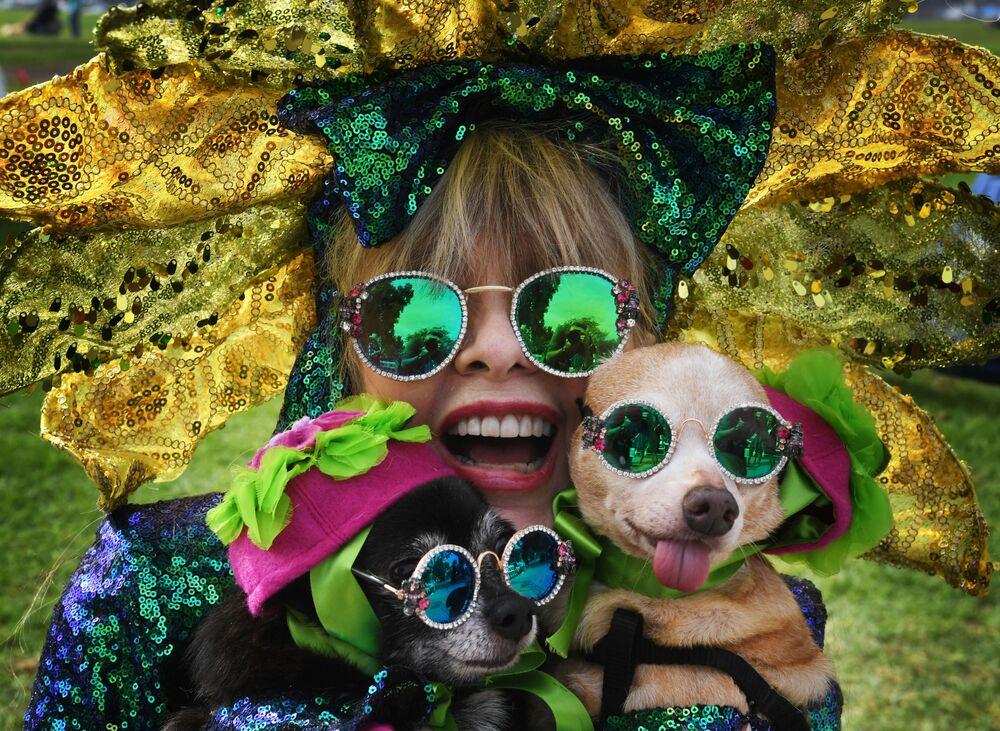 Mulher e seus dois cachorros esperam o início do desfile anual Haute Dog Halloween, em Long Beach, Califórnia (EUA), 28 de outubro de 2018