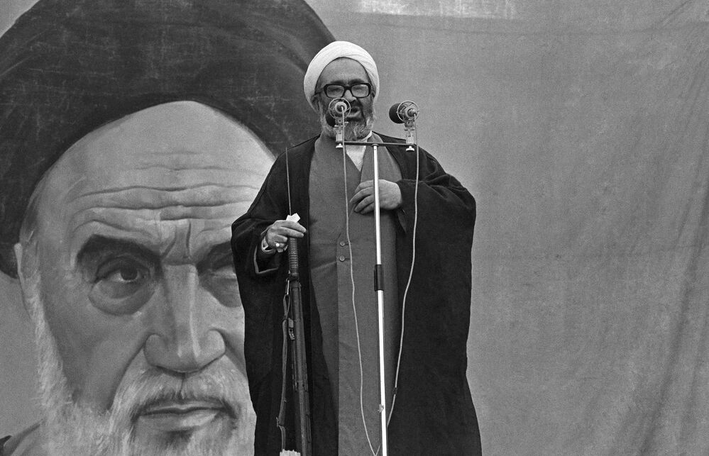 Aiatolá Hussein Ali Montazeri segura um rifle ao afirmar durante um discurso que os reféns não seriam libertados até que o xá Reza Pahlavi fosse entregue ao Irã, em 23 de novembro de 1979