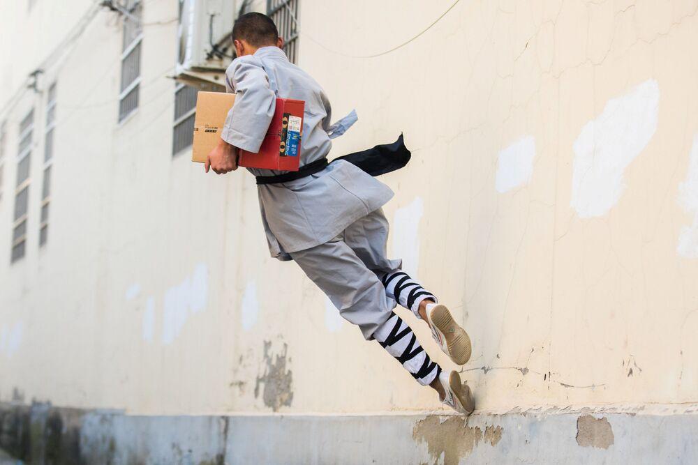 Homem vestido de traje de kung-fu entrega encomendas na véspera do Dia dos Solteiros, na China