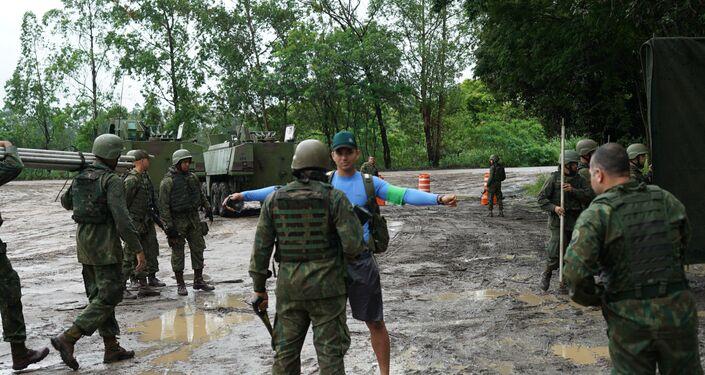 Militar disfarçado de civil é revistado antes de ser resgatado durante a Operação Atlântico