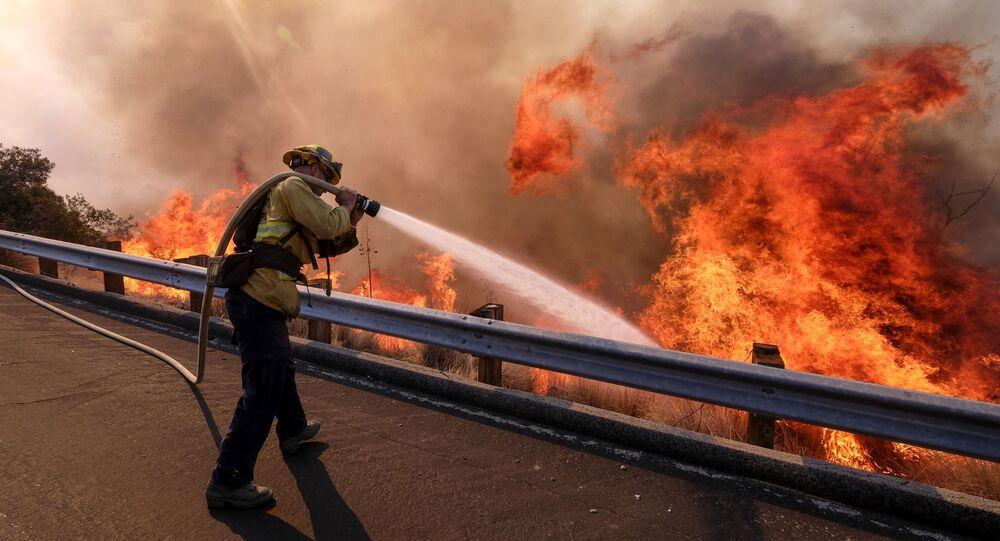 Bombeiro combate incêndio em uma estrada de Simi Valley, Califórnia, em 12 de novembro de 2018