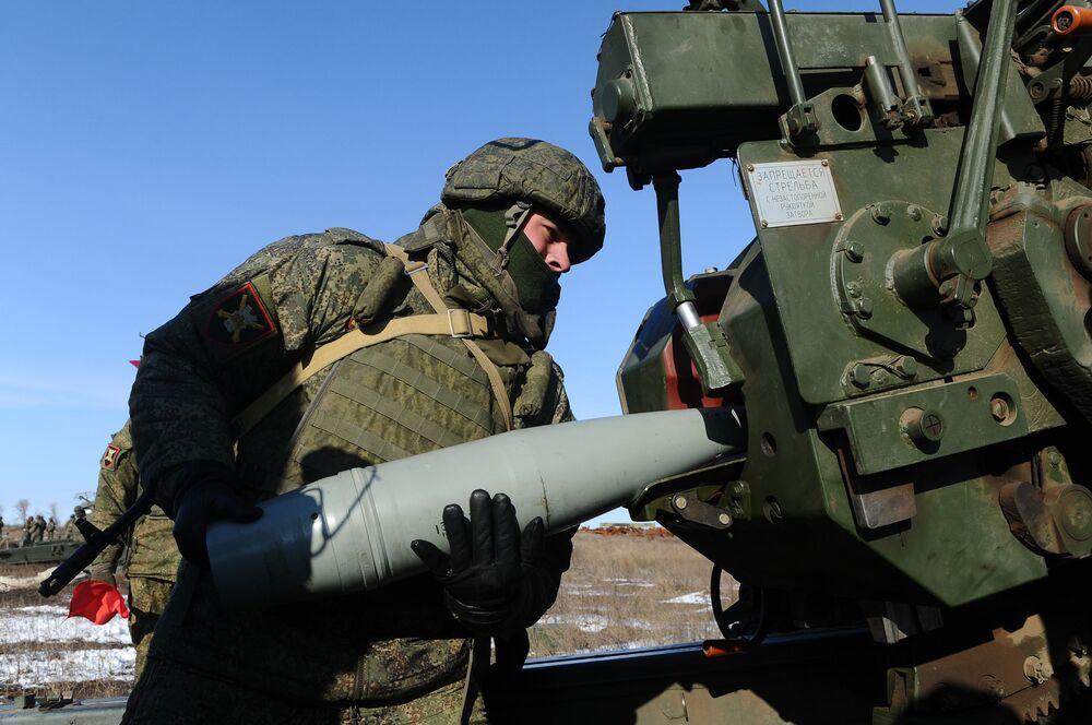 Militar carrega um projétil no obuseiro 2А65 durante preparação para exercícios de tiro real