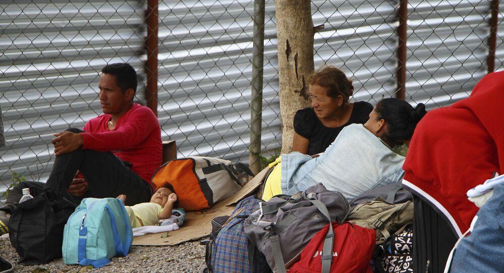 Imigrantes venezuelanos descansam ao lado de seus pertences após cruzarem a fronteira até Pacaraíma, em Roraima.