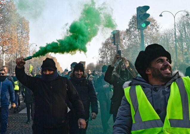 Participantes de protestos dos coletes amarelos contra o aumento dos preços de combustíveis em Paris