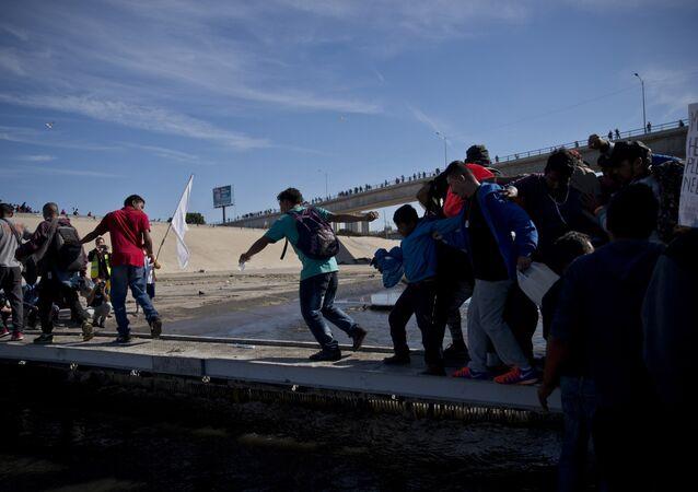 Migrantes atravessam rio na fronteira entre México e EUA após passar por uma linha da polícia mexicana na travessia do Chaparral em Tijuana. México, domingo, 25 de novembro de 2018.