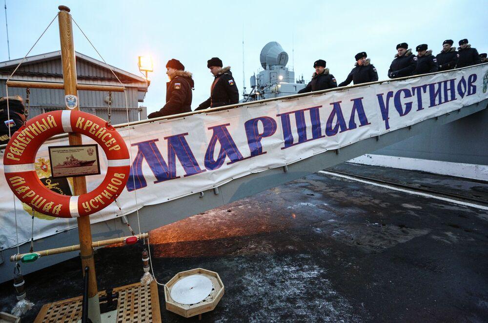 Tripulantes do cruzador de mísseis Marshal Ustinov desembarcam no cais da Frota do Norte russa em Severomorsk