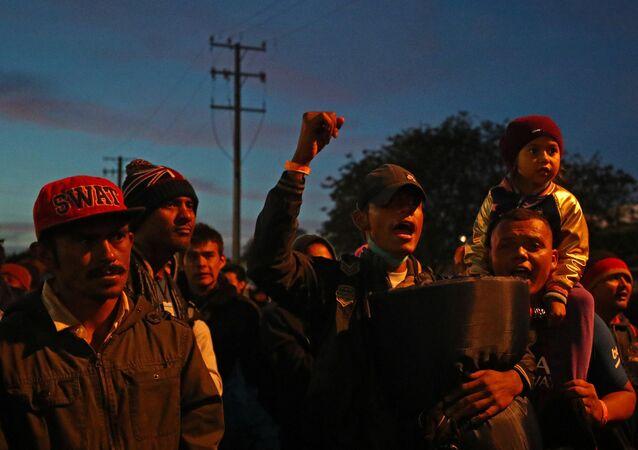 Os migrantes, parte de uma caravana de milhares de pessoas da América Central que tentam chegar aos Estados Unidos, ficam do lado de fora do porto de El Chaparral de passagem de fronteira entre o México e os Estados Unidos.