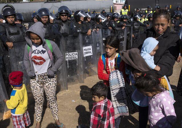 Migrantes contidos pela polícia mexicana na fronteira em Tijuana, México.