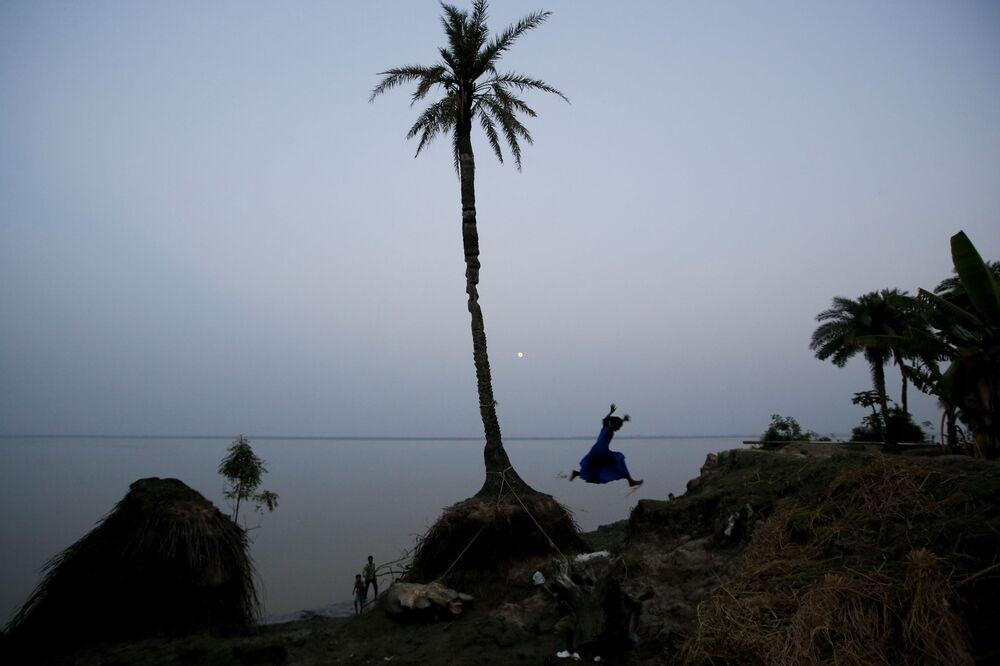 Criança brincando na costa da ilha que está desaparecendo.