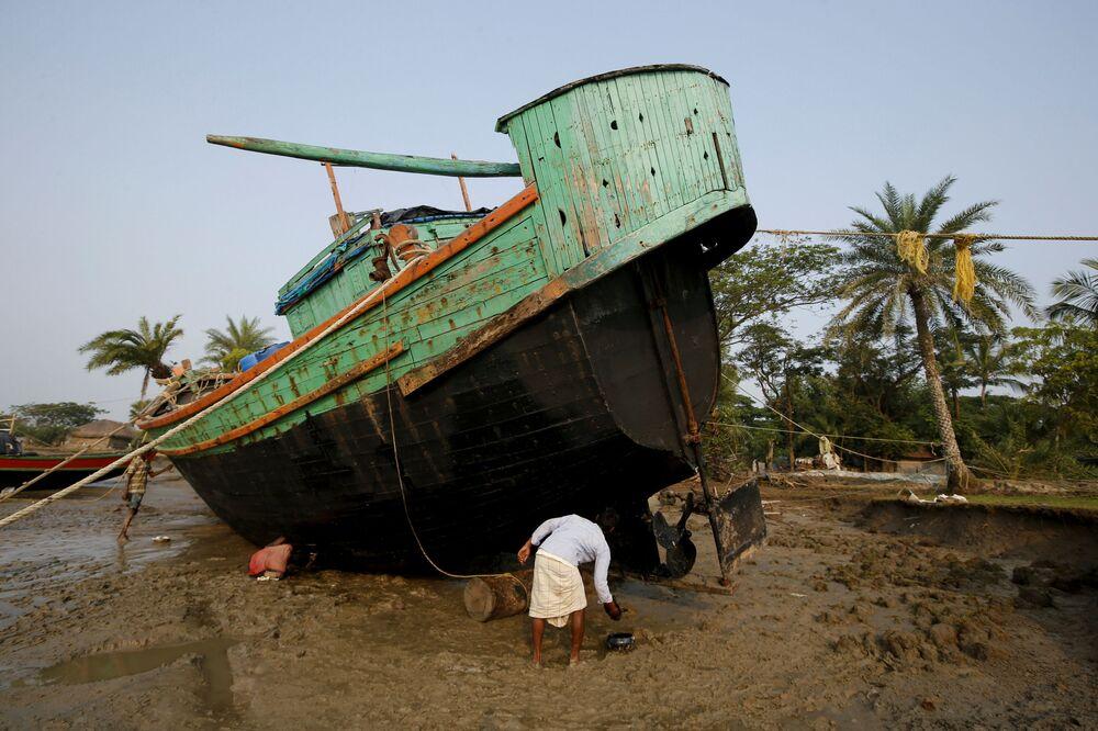 Trabalhadores reparando um barco na costa da ilha.