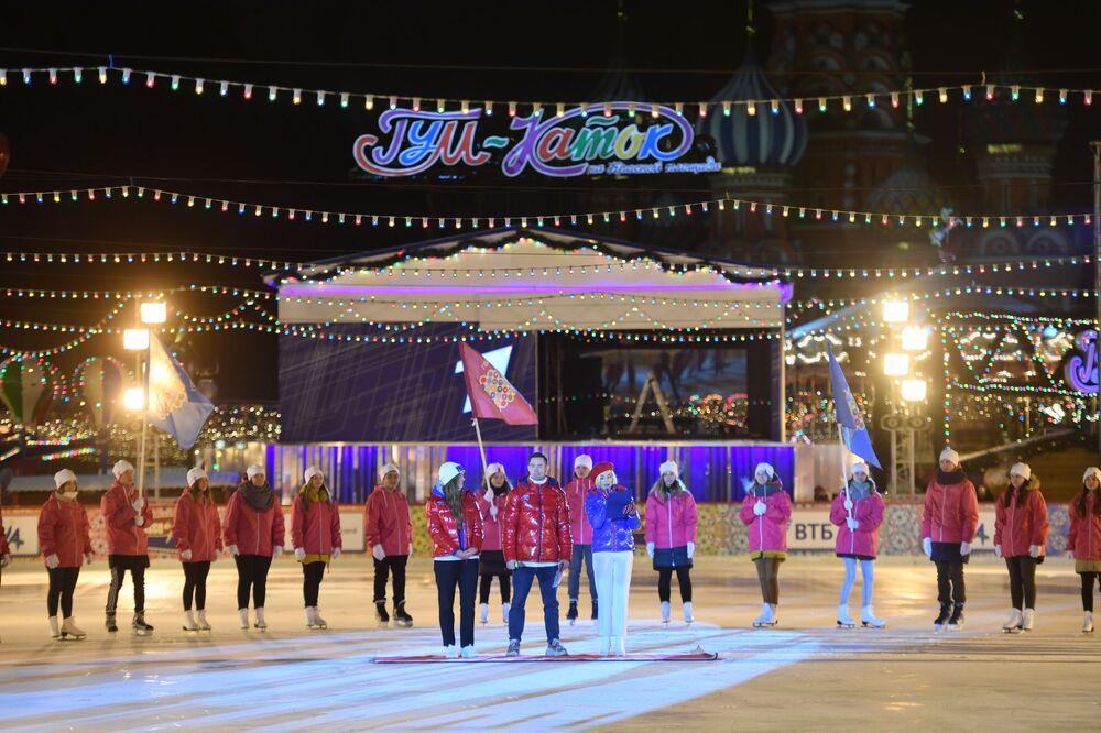 Ao lado da pista se encontra uma feira natalina decorada com luzinhas, árvores de natal e ornamentos brilhantes.