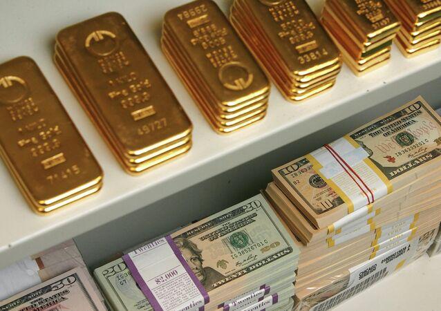 Barras de ouro e notas de dólar dos EUA são retratados dentro de cofre em um banco em Viena, Áustria, 21 de julho de 2009