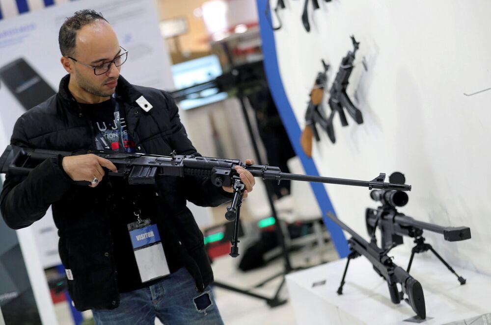 Visitante segura uma arma na Feira Internacional de Defesa EDEX 2018 no Egito