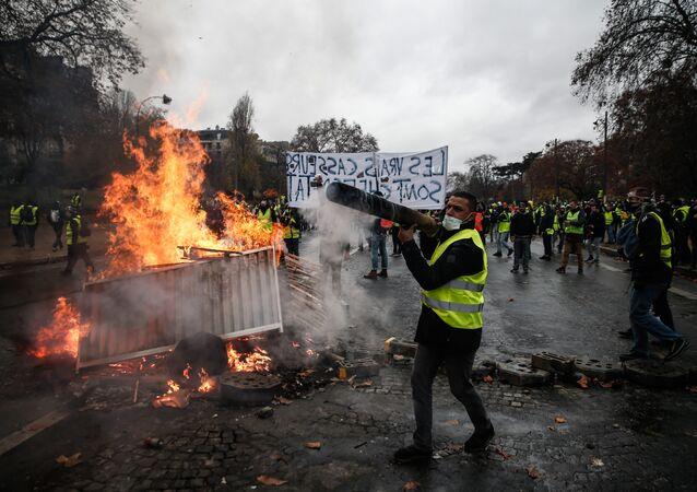 Manifestantes constroem uma barricada durante um protesto dos Coletes Amarelos (Gilets jaunes) contra o aumento dos preços do petróleo e os custos de vida.