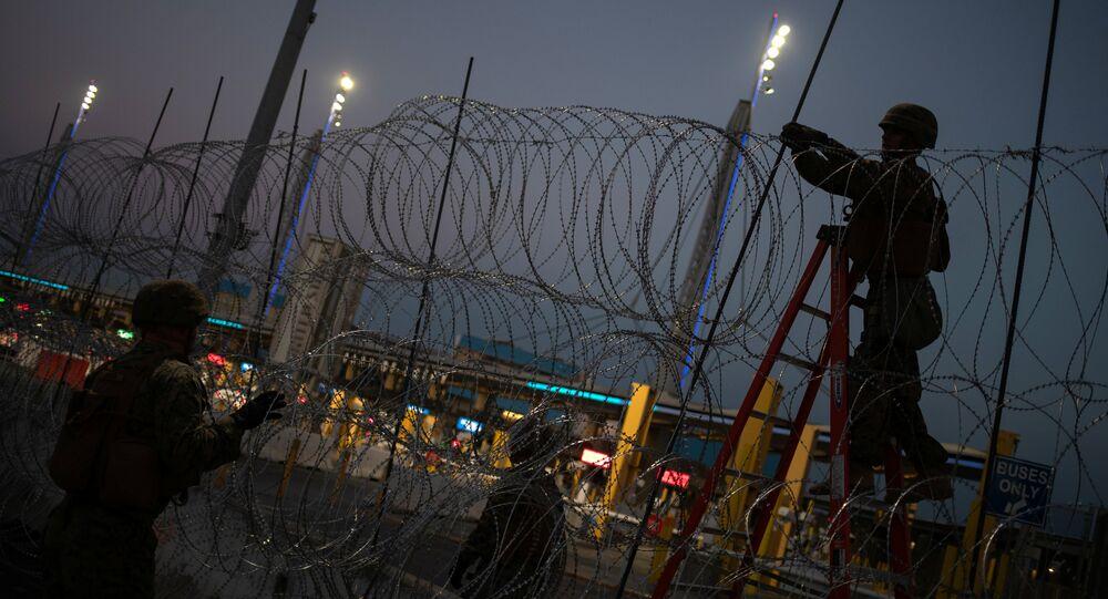 Os fuzileiros navais dos Estados Unidos fortificam o arame farpado na cerca fronteiriça do porto de San Ysidro em Tijuana, México.