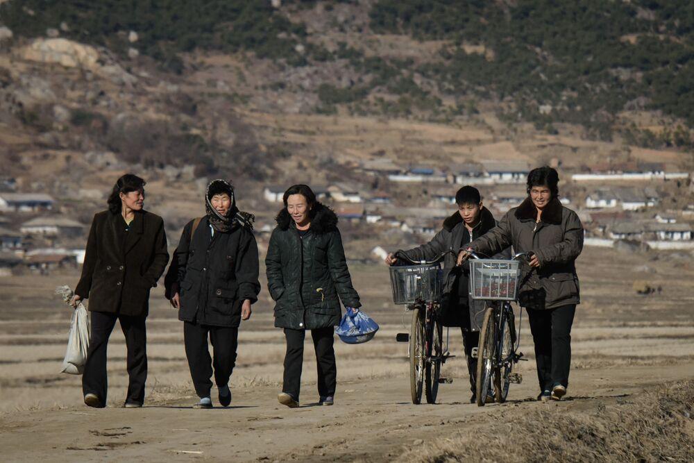 Um grupo de mulheres anda por uma via na cidade norte-coreana de Chonchon