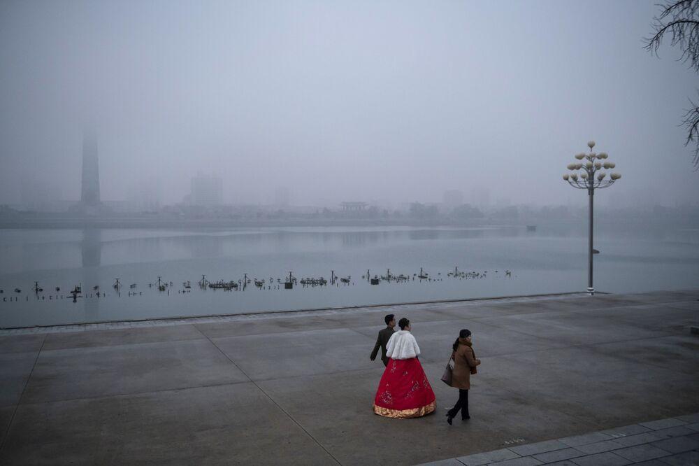 Noiva e noivo fazem passeio às margens do rio Taedong, Pyongyan