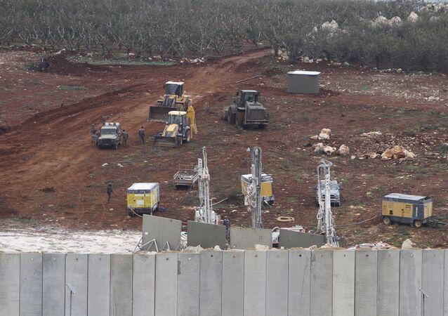 Veículos militares israelenses trabalham próximo de uma parede construída por Israel nas proximidades da fronteira com o Líbano