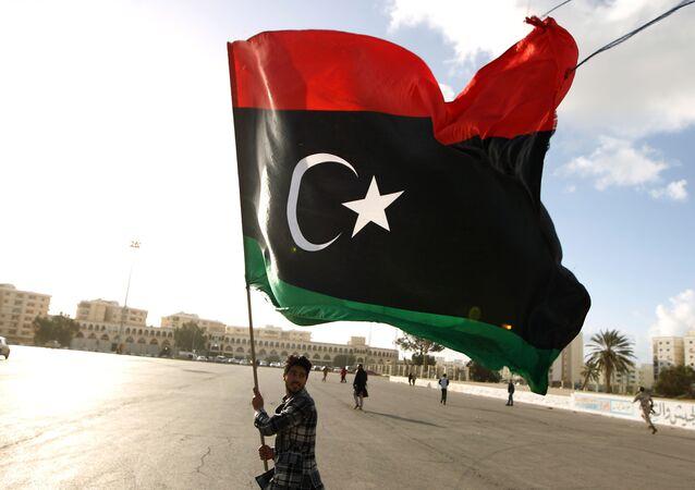 Líbio agita bandeira nacional enquanto manifestantes se reúnem para protesto contra a munição do Exército líbio, na cidade de Benghazi (foto de arquivo)