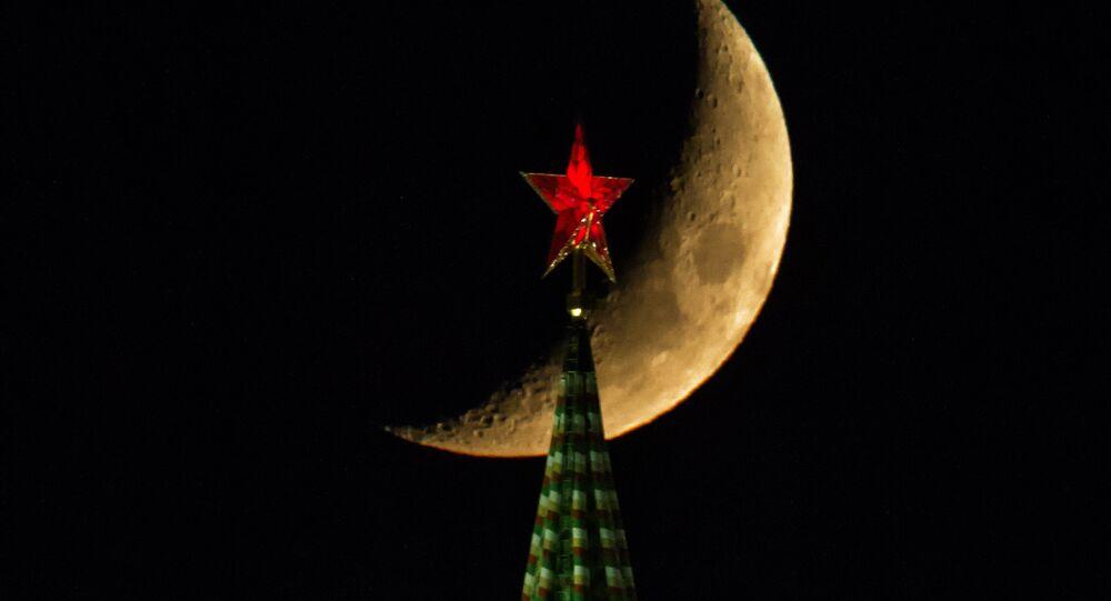 A lua sobre a torre Spasskaya do Kremlin de Moscou