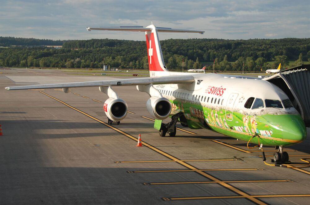 Aeronave Avro RJ100 pertencente à Swiss International Air Lines notado na pista de pouso pelo verde limão na parte de baixo da fuselagem