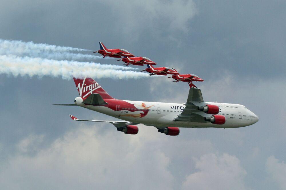 O Boeing 747-400 da empresa Virgin é acompanhado por um grupo de pilotagem da Força Aérea Real britânica Red Arrows (Estrelas Vermelhas)