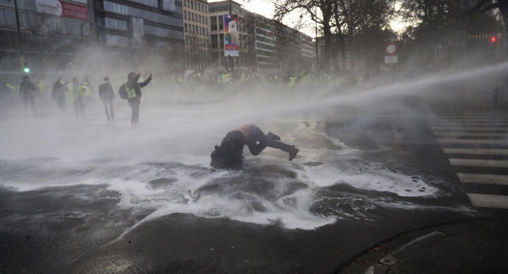 Manifestante é atingido por canhão de água durante protesto dos 'coletes amarelos' em Bruxelas.