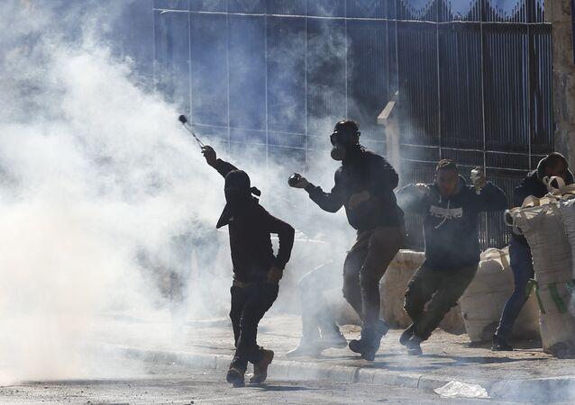 Manifestantes palestinos durante conflito com tropas israelenses, na Cisjordânia