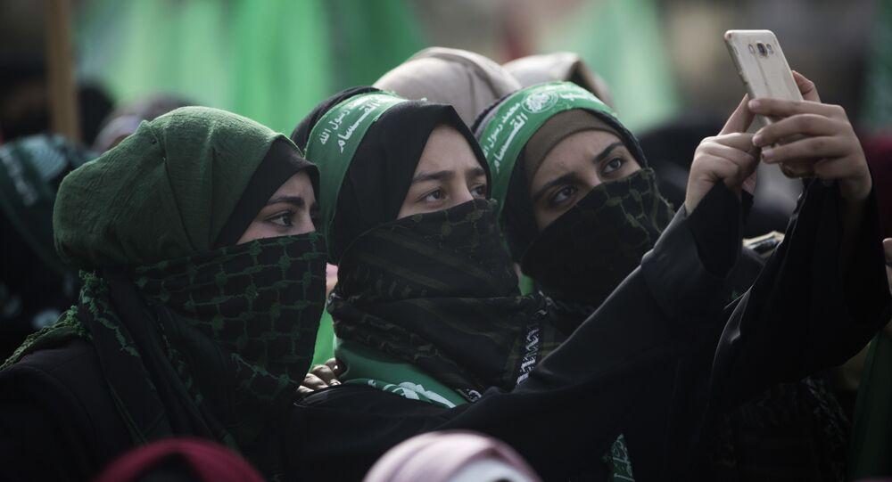 Mulheres tiram selfie em manifestação de comemoração do aniversário da fundação do Hamas em Gaza.