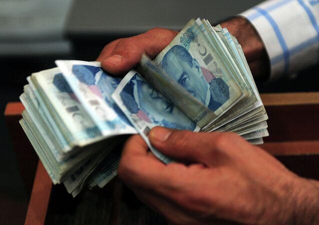 Um cambista conta notas de lira turca em Istambul (arquivo)
