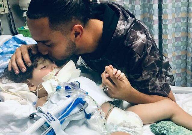 O menino Abdullah Hassan e o pai, Ali na UTI do Hospital Pediátrico Benioff, Califórnia.