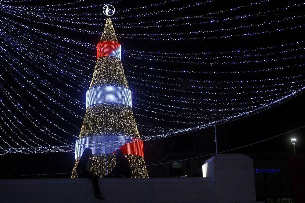 Duas garotas sentadas em torno de uma árvore de Natal na Praça Salvador do Mundo, em El Salvador.