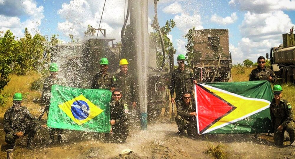 Militares brasileiros posam com bandeiras do Brasil e da Guiana diante de poço artesiano.