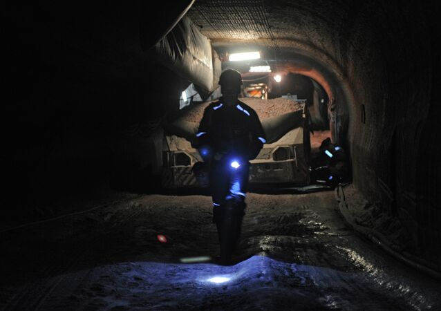 Empregado em equipamento especial andando na mina